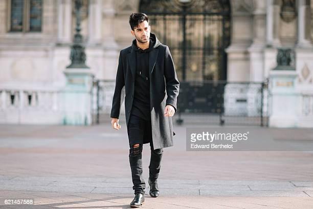 Anil Brancaleoni is wearing Bose QC35 silver headphones a Sandro black long coat a Maniere de Voir pull over Maniere de Voir black ripped pants...