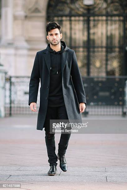 Anil Brancaleoni is wearing Bose QC35 silver headphones a Sandro black long coat a Maniere de Voir pull over Maniere de Voir black ripped pants...