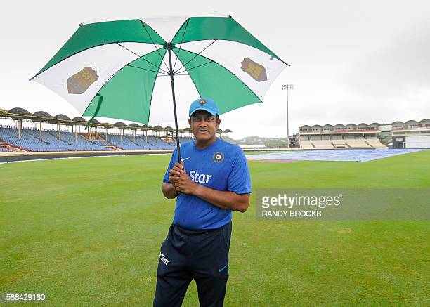Anil Kumble head coach of India inspects the water filled field due to overnight rain on day 3 of the 3rd Test between West Indies and India on...