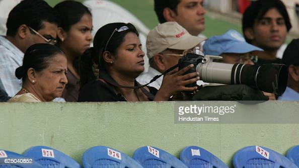 Anil Kumble's sisterinlaw Romila shoots while his mother watch him play during the third day of the third test match between India and Pakistan at...