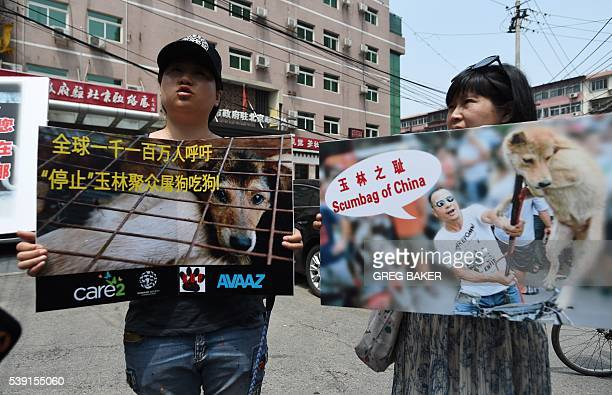 Animal activists display protest banners outside the Yulin government office in Beijing on June 10 2016 A group of Chinese and international animal...