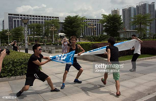 Animal right activists scuffle with unidentified people as they protest against a dog meat festival in front on the government building in Yulin in...