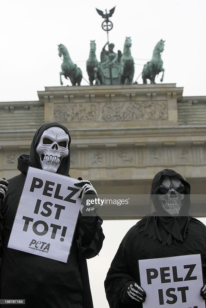 Animal rights activists from PETA (People for the Ethical Treatment of Animals) dressed up as death hold posters reading 'Fur is death' as they demonstrate during an anti-fur protest action on November 21, 2012 in front of the Brandenburg Gate in Berlin. LAFARGUE