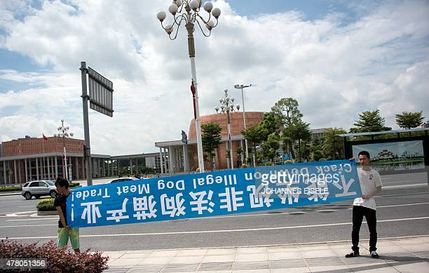 Animal rights activists hold a banner that reads 'Crack Down on Illegal Dog Meat Trade' as they protest against a dog meat festival in front on the...