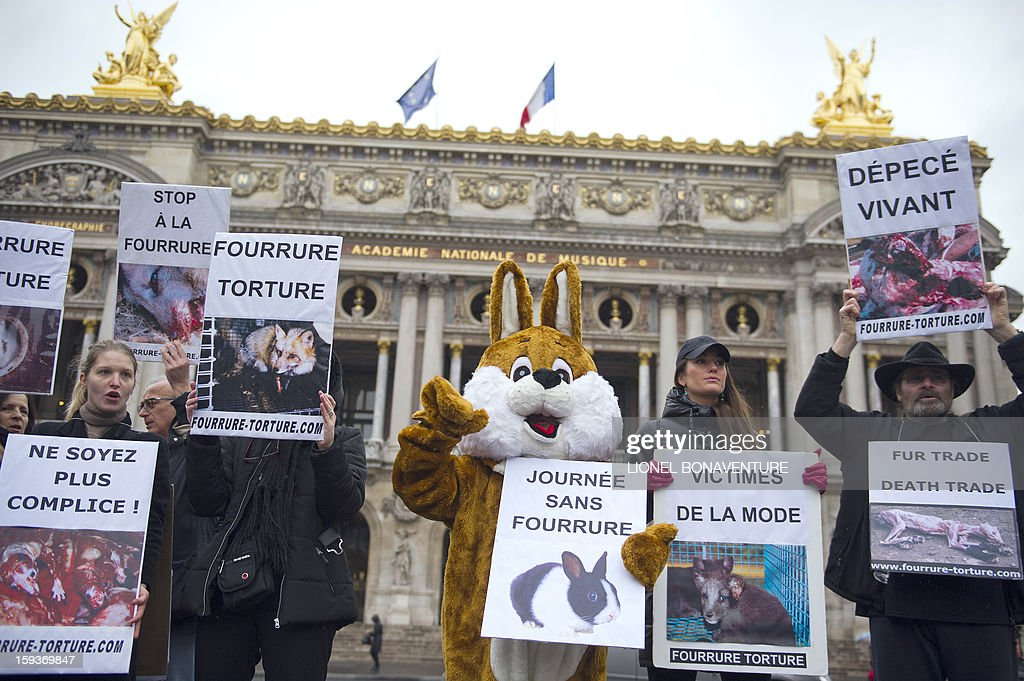 Animal rights activists hold placards in front of the Opera on January 12, 2013 in Paris, to protest against cruelty towards animals and the use of fur in the fashion industry, during a nationwide anti-fur demonstration called by French association 'Fourrure Torture' (Fur Torture). AFP PHOTO LIONEL BONAVENTURE