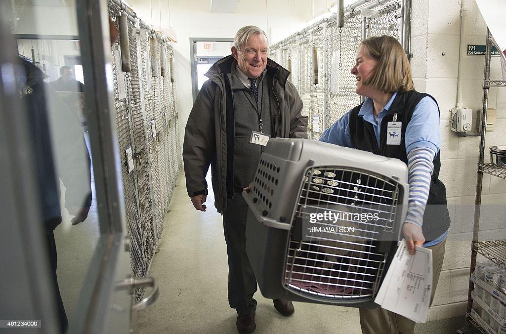 Animal Welfare League of Alexandria Director of Animal Care Abbie Hubbard helps Animal Welfare League of Arlington President and CEO Neil Trent carry...