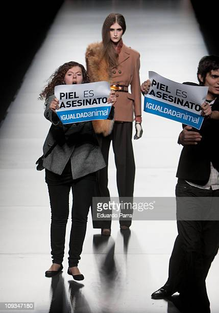 Animals rights campaigners protest against the use of fur on the runway with the slogan 'fur is murder' during the Ion Fiz Maria Escote Fashion Show...