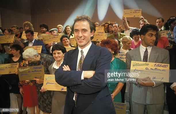 L'animateur Philippe Risoli avec les gagnants lors de la présentation de la 100ème émission télévisee 'Le Millionnaire' sur TF1 le 29 septembre 1992...