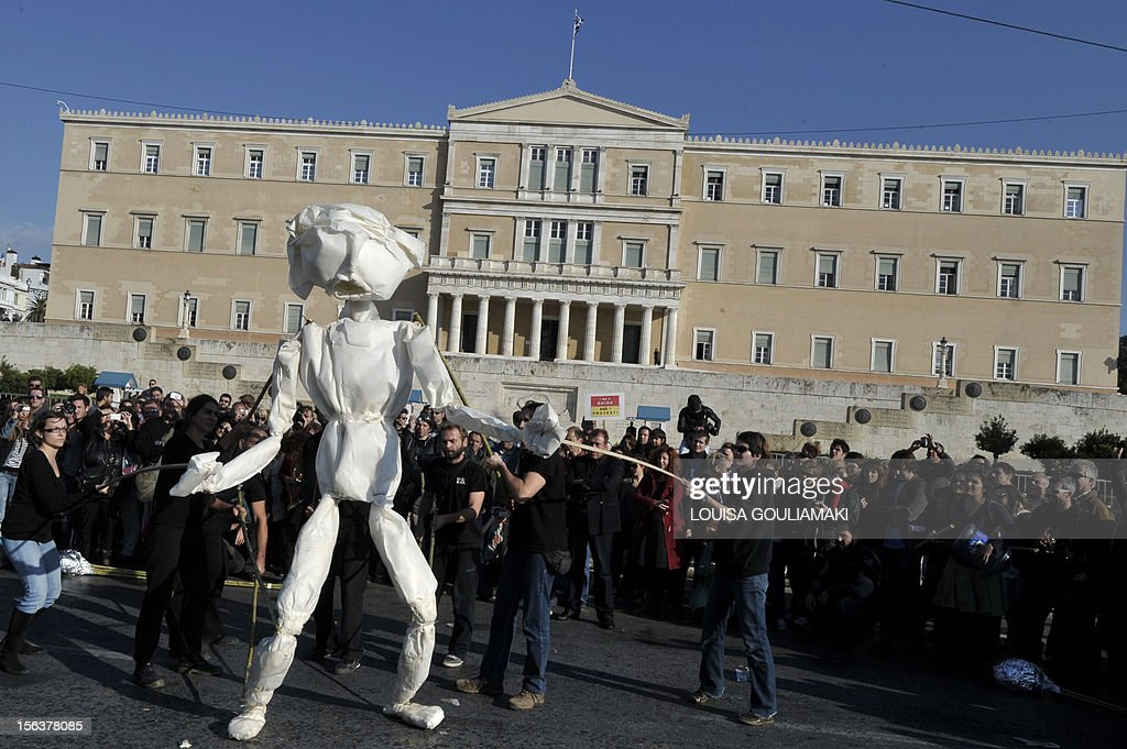 Animateurs from a Greek puppet center stage a performance outside the Greek parliament in Athens, during an anti-austerity protest on November 14, 2012. Workers in southern Europe launched an unprecedented string of strikes and walk-outs against austerity cuts Wednesday, halting some factories and grounding more than 700 flights. AFP PHOTO / LOUISA GOULIAMAKI