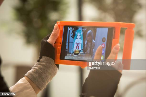 Anime fan takes photo of their virtual idol Hatsune Miku in a phone equipped with augmented reality application during an event in Sendai Japan on...