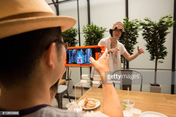 Anime fans holding a smart phone equipped with augmented reality application takes photo with her virtual idol Hatsune Miku while having some sweets...
