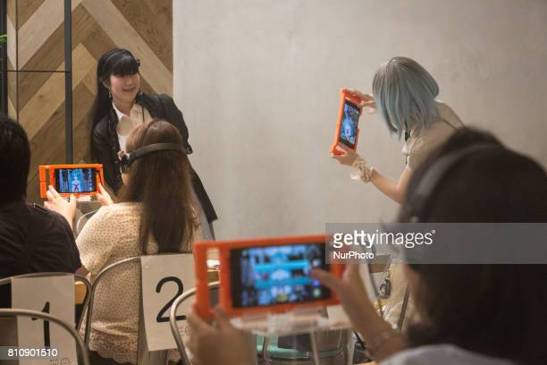 Anime fans takes photo of their virtual idol Hatsune Miku in a phone equipped with augmented reality application during an event in Sendai Japan on...