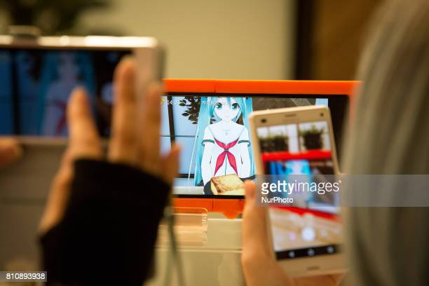 Anime fans takes photo of their virtual idol Hatsune Miku in a smart phone equipped with augmented reality application during an event in Sendai...
