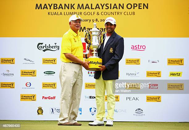 Anirban Lahiri of India is presented with the trophy by Prime Minister of Malaysia Abdul Razak after victory during the final round of the Maybank...
