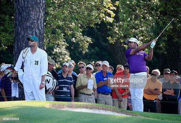 Anirban Lahiri of India plays a shot on the first hole as his caddie Laddie Cline looks on during the first round of the 2015 Masters Tournament at...