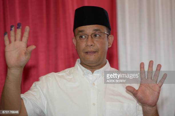 Anis Baswedan a candidate for Jakarta governor gestures after casting his ballot in Jakarta on April 19 2017 Jakarta's Christian governor on April 19...