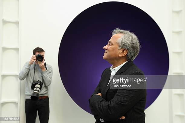 Anish Kapoor poses in front of a piece of his work entitled 'Two Blues' during a press preview at the Lisson Gallery on October 9 2012 in London...