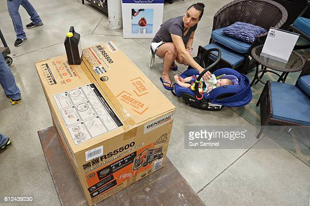 Anita Baranyi keeps an eye on the generator she is purchasing while feeding her 6monthold baby Rufus Nagygyorgy on Tuesday Oct 4 2016 at Lowe's in...