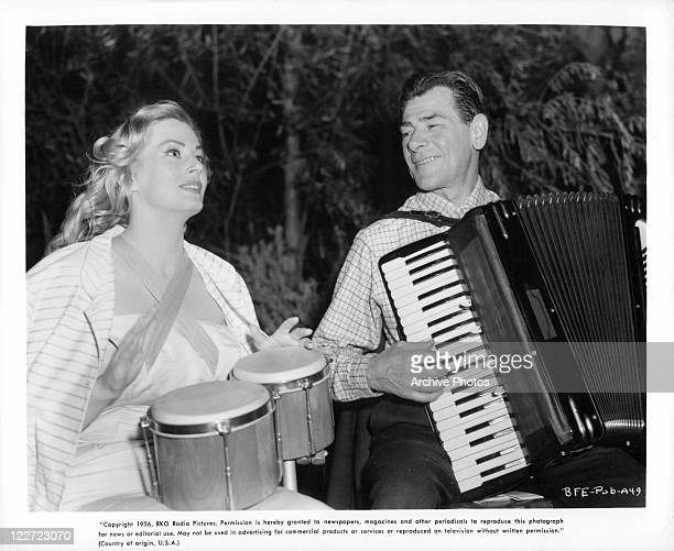 Anita Ekberg plays drums as Tony Travers plays accordian in a scene from the film 'Back From Eternity' 1956