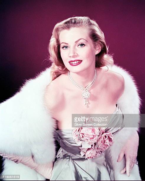 Anita Ekberg Swedish model and actress glamorous in a lowcut dress with flowers covering her cleavage a white fur stole and a pearl necklace with...