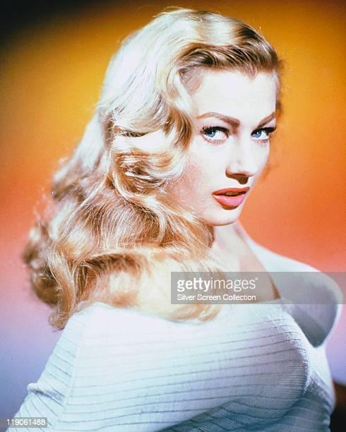 Anita Ekberg Swedish model and actress posing in a studio portrait against an orange background circa 1955