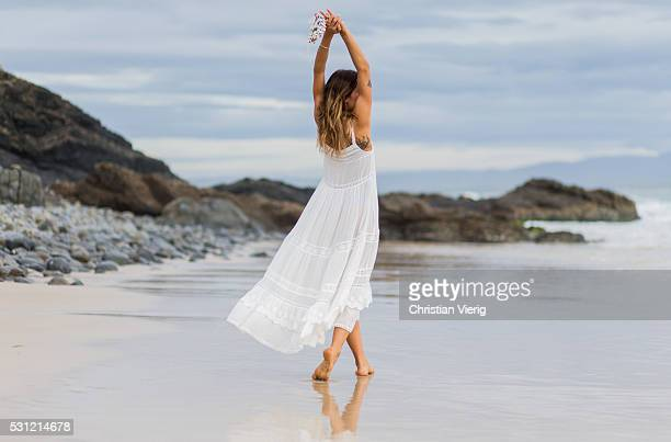 Anita Ghise poses in front of the ocean wearing a a long white boho chic summer dress from Spell Byron Bay on May 13 2016 in Byron Bay Australia