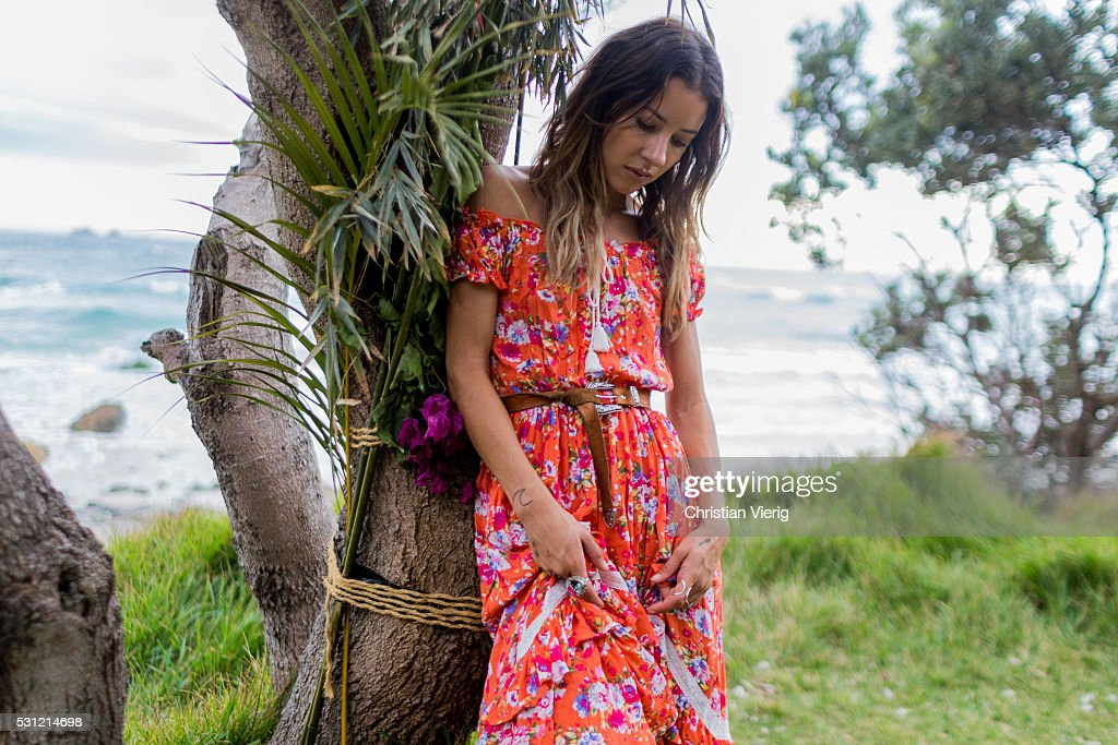 Anita Ghise wearing a long strapless red orange boho chic dress with floral print from Spell Byron Bay on May 13 2016 in Byron Bay Australia
