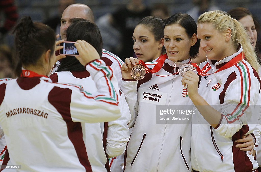 Anita Gorbicz (C) and Kinga Klivinyi (R) of Hungary posing with medals celebrate with the trophy during the Women's European Handball Championship 2012 medal ceremony at Arena Hall on December 16, 2012 in Belgrade, Serbia.