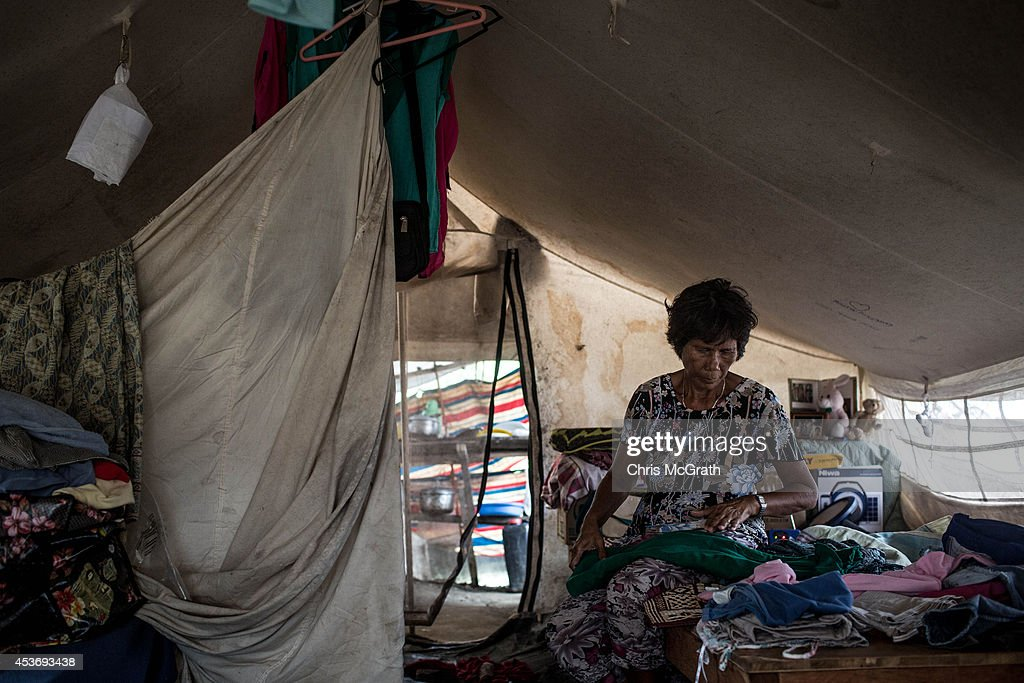 Anita Latay folds clothes in her temporary tent home, shared by two families in the San Jose evacuation complex on August 16, 2014 in Tacloban, Leyte, Philippines. Many families are still housed in temporary tent housing in the San Jose district. The families have been told that they will be rehoused before the visit of Pope Francis. Residents of Tacloban city and the surrounding areas continue to focus on rebuilding their lives nine months after Typhoon Haiyan struck the coast on November 8, 2013, leaving more than 6000 dead and many more homeless. With many businesses and government operations back up and running and with the recent start of the years typhoon season, permanent housing continues to be the main focus with many families still living in temporary accommodation. As well as continuing recovery efforts Leyte is preparing for the arrival of Pope Francis, who will visit the region from January 15- 19.