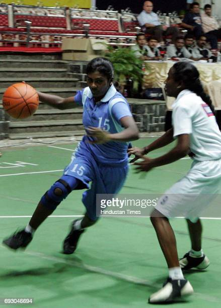 Anita P of Southern Railway takes control of the ball from Lincy Jose of Maharashtra in the league match of the Savio Cup Allindia Basketball...