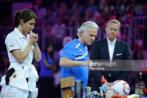 Anja Kling and Nino de Angelo attend a game while presenter Johannes B Kerner watches them during the 'Deutschland Gegen Italien' TV Show on April 20...