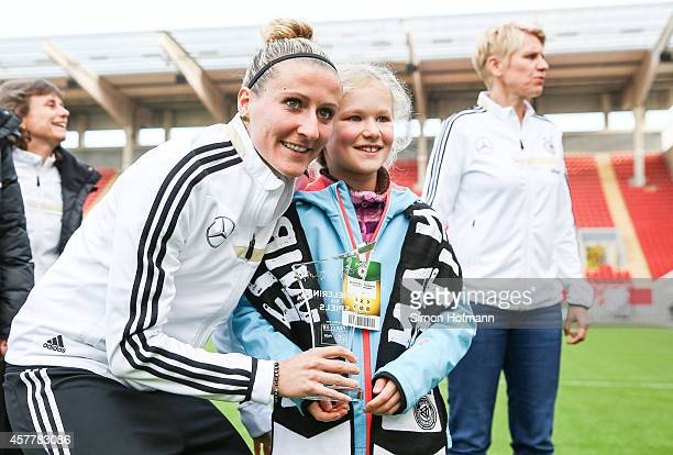 Anja Mittag is awarded as player of the match by supporter Mathilda prior to a Germany Women's Training Session on October 24 2014 in Offenbach...