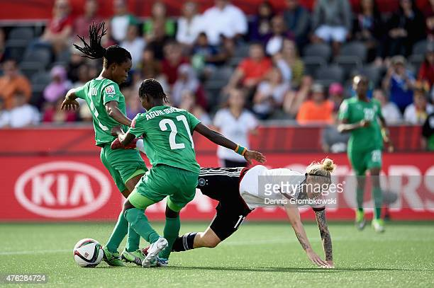 Anja Mittag of Germany is challenged by Sophie Aguie and Fatou Coulibaly of Cote D'Ivoire during the FIFA Women's World Cup Canada 2015 Group B match...