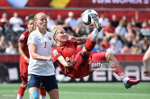Anja Mittag of Germany takes a shot under the pressure of Marita Skammelsrud Lund of Norway during the FIFA Women's World Cup Canada 2015 Group B...