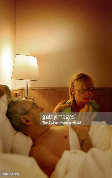 Anjelika Elliott sits and talks to her husband Dr John Elliott who is wracked with pain as he attempts to rise from his hotel room bed in Zurich 26...