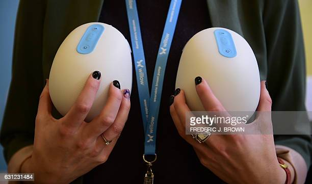 Anke Huiskes holds for display the Smart Breast Pump from Willow two individual motorized cups for mothers to slip into their nursing bras and go...