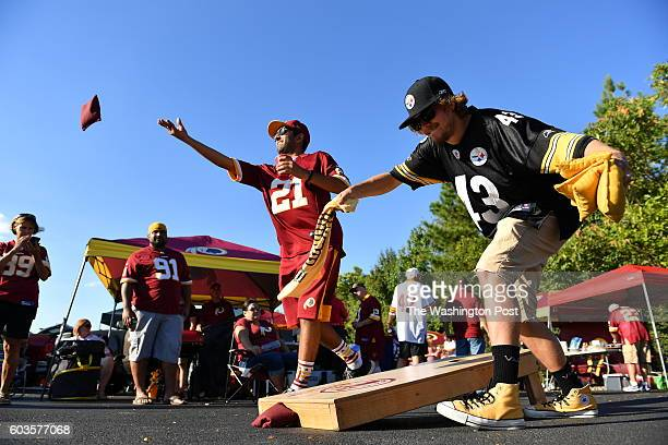 Ankit Mittal of Ellicott City Md tosses a bean bag as his friend Shean Flynn of Newport News Va waves his Terrible Towel as the two were playing Corn...