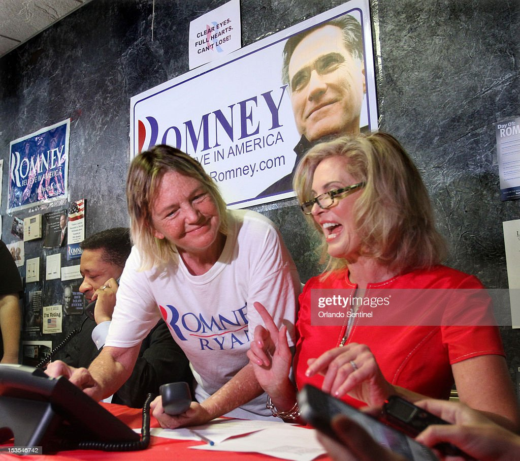 Ann Romney wife of Republican presidential nominee Mitt Romney gets help from volunteer Sarah Frazee center as she works the phones with Artur Davis...