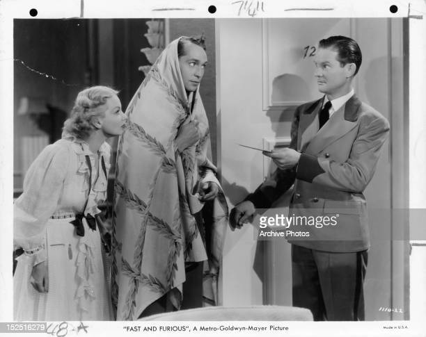 Ann Sothern and Franchot Tone are handed note at the door in a scene from the film 'Fast And Furious' 1939