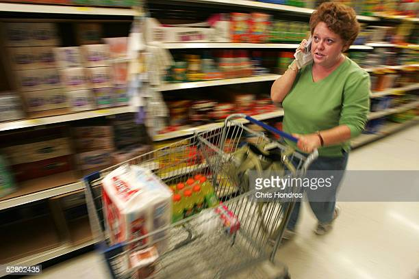 Ann Zimpfer of St Louis County chats on her cell phone while shopping the aisles of a WalMart May 11 2005 in St Louis County Missouri WalMart...