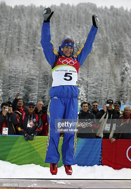 Anna Carin Olofsson of Sweden jumps on the podium after winning the gold medal in the Womens Biathlon 125km Mass Start Final on Day 15 of the 2006...