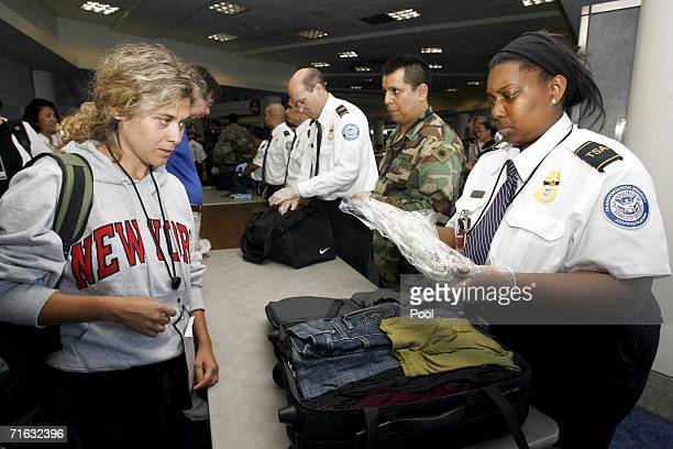 Anna Carriero of Italy watches as Transportation Security Administration worker Tracy Albert goes through Carriero's carryon bags at the American...