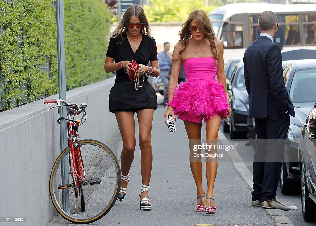Anna Dello Russo and assistant Carlotta Oddi seen at Milan Fashion Week Menswear Spring/Summer 2014 on June 23, 2013 in Milan, Italy. Anna is wearing a OScar De La Renta dress.
