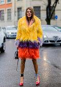 Anna dello Russo is wearing a yellow pruple red fur coat a grey mini Chloe bag and red Miu Miu heels seen outside Giorgio Armani during Milan Fashion...
