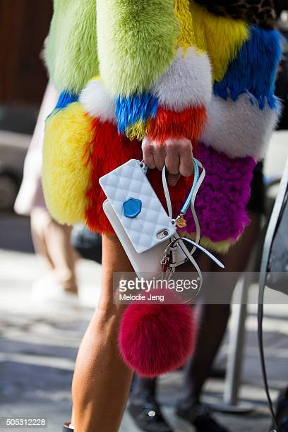 Anna Dello Russo wears a multicolored Saint Laurent fur coat and carries a 'Cliche' phone case and a fur pom pom during the Milan Men's Fashion Week...