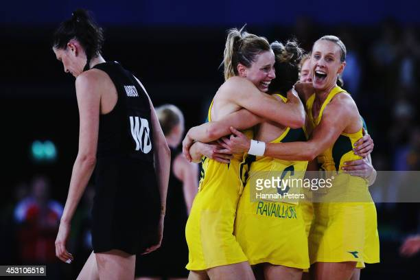 Anna Harrison of New Zealand walks off as Laura Geitz Kimberley Ravaillion and Renae Hallinan of Australia celebrate winning the gold medal match...