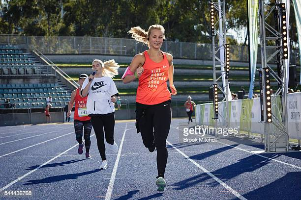 Anna Heinrich races to the finish line as Carissa Walford cheers her on at the Nike Women's Half Marathon at Sydney Olympic Park on July 3 2016 in...