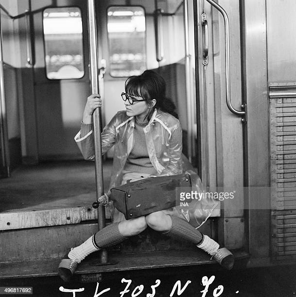 Anna Karina sat on walking in the entrance of a car of commuter train