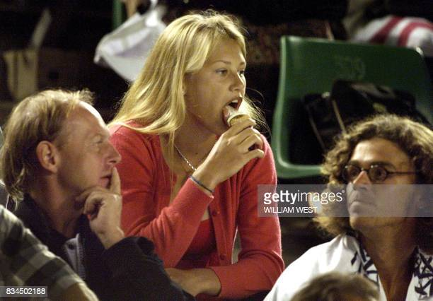Anna Kournikova of Russia licks icecream from a cone while sitting in the players' seating area watching the men's quarterfinal match between Nocolas...