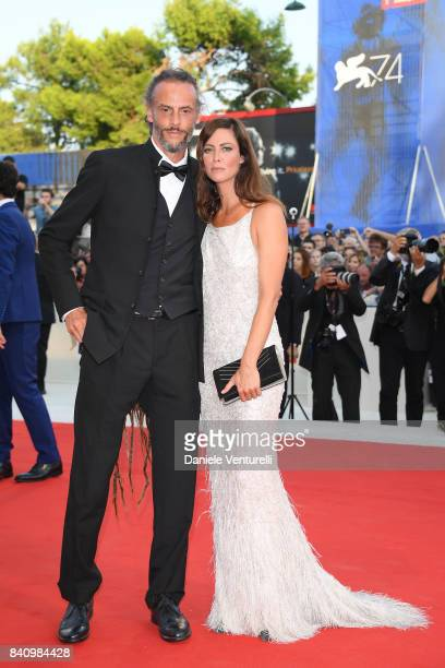 Anna Mouglalis and a guest walk the red carpet ahead of the 'Downsizing' screening and Opening Ceremony during the 74th Venice Film Festival at Sala...